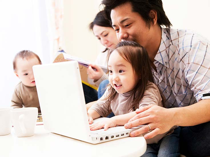 A family with two young children playing on a laptop