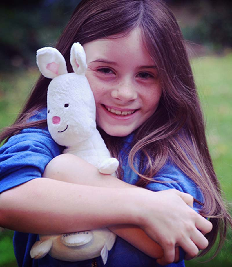 A young girl hugs a WSECU Munny Bunny stuffed animal