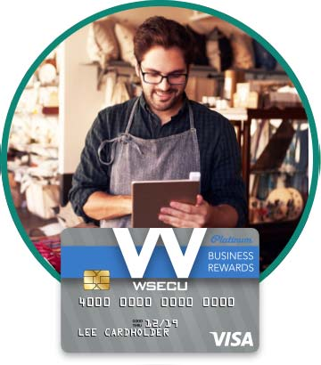 Store owner in apron holding tablet. Image of WSECU Platinum Business Rewards Visa card below.