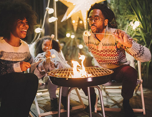 couple sitting around fire roasting marshmallows on a patio