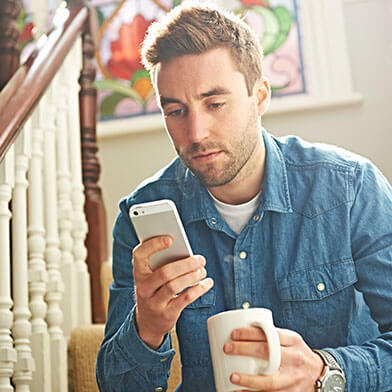 Man drinking coffee while looking at phone