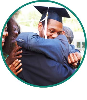 A graduate in a cap and gown hugging his father